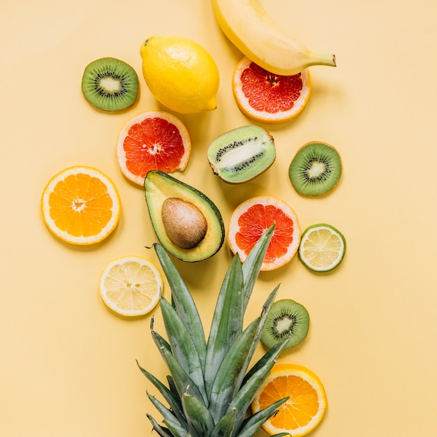 Various fruits near pineapple leaves Free Photo