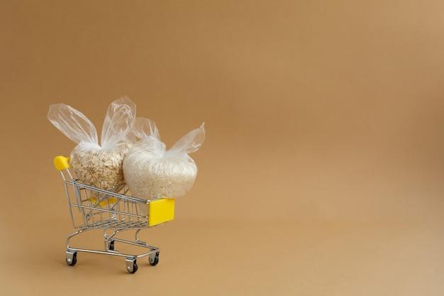 갈색 배경에 식료품 카트에 패키지에 다양 한 가루. 쌀과 오트밀 프리미엄 사진