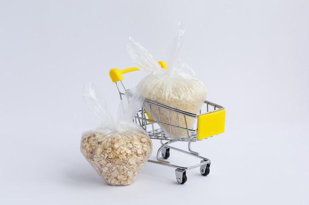 흰색 배경에 식료품 카트에 패키지에 다양 한 가루. 쌀과 오트밀 프리미엄 사진