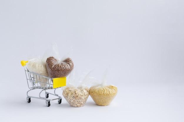 흰색 바탕에 식료품 장바구니에 패키지에 다양 한 가루. 쌀과 오트밀, 메밀, 기장 프리미엄 사진