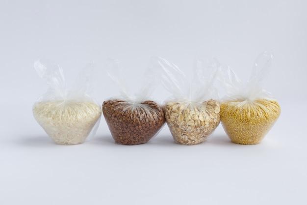 흰색 바탕에 작은 비닐 봉지에 다양 한 가루. 쌀과 오트밀, 메밀과 기장 프리미엄 사진
