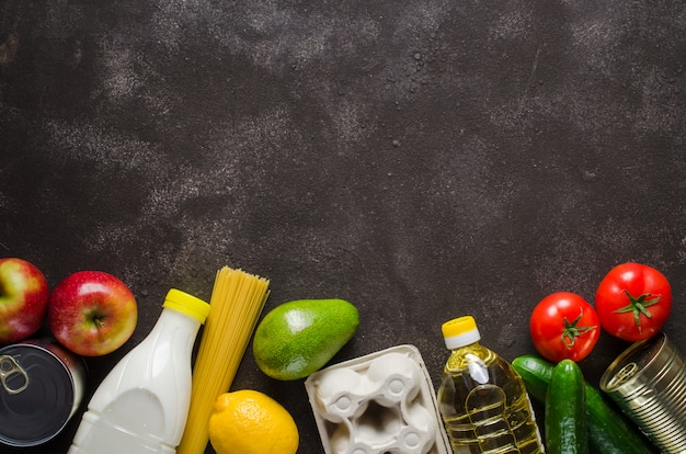 Various groceries on dark concrete background. food delivery concept. food donations. Premium Photo