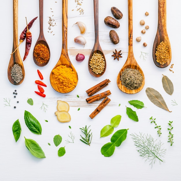 Various herbs and spices in wooden spoons on wooden background. Premium Photo