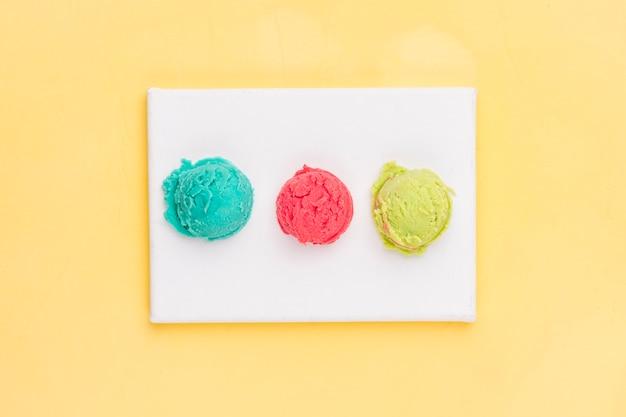 Various ice cream balls on white board Free Photo