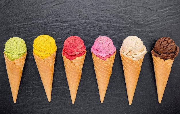 Various of ice cream flavor in cones set up on dark stone Premium Photo