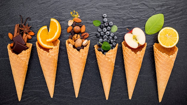 Various of ingredient for ice cream flavor in cones set up on dark stone Premium Photo