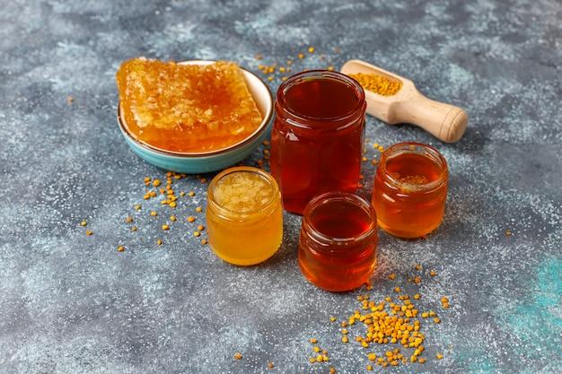 ガラスの瓶、ハニカム、花粉の蜂蜜の様々な種類。 無料写真
