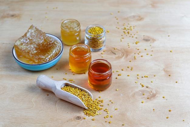 ガラスの瓶、ハニカム、花粉に含まれるさまざまな種類の蜂蜜。 無料写真