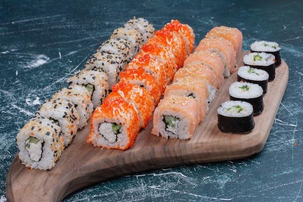 На деревянной тарелке подаются различные виды суши-роллов. Бесплатные Фотографии