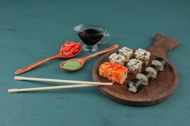 青いテーブルに生姜の酢漬け、わさび、醤油を添えた各種巻き寿司。 無料写真