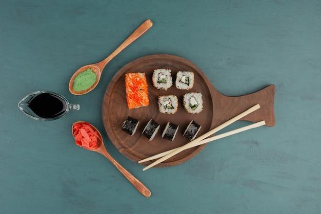 파란색 테이블에 절인 생강, 와사비, 간장을 곁들인 다양한 종류의 스시 롤 플레이트. 무료 사진