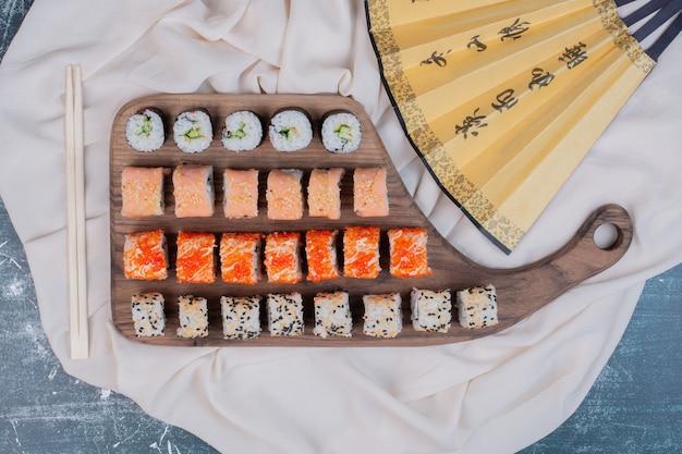 Vari tipi di involtini di sushi serviti su un piatto di legno con bacchette e ventaglio giapponese. Foto Gratuite