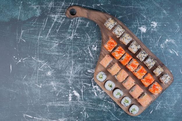 Vari tipi di rotoli di sushi serviti su un piatto di legno. Foto Gratuite