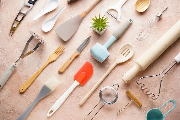 Various kitchen utensils on a beige background, top view. Premium Photo