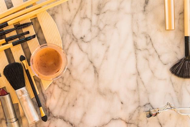 Various makeup brushes; mascara; honey with eyelash curler on marble backdrop Free Photo