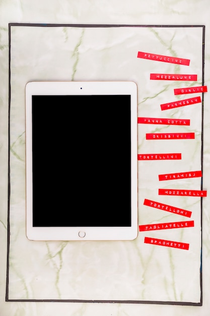 Various menus beside digital tablet with blank black screen Free Photo