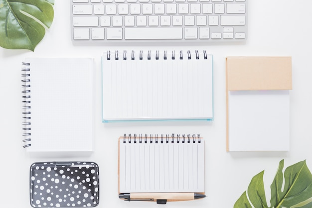 Various notebooks and keyboard on white desk Free Photo