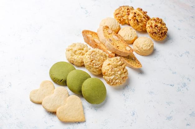 Biscotti vari della noce biscotti della noce, biscotti dell'arachide, biscotti di mandorla e biscotti di matcha sulla tavola leggera Foto Gratuite