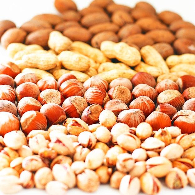 Various nuts selection: hazelnuts, pistachio and pecans in glass Free Photo