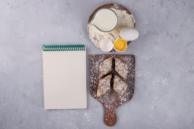 木製の大皿にノートと一緒に様々なペストリーや食材 無料写真