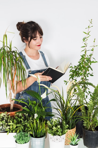 Various potted plants in front of female florist holding diary Free Photo