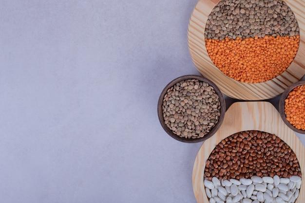 木製のボウルにさまざまな生豆とレンズ豆。 無料写真