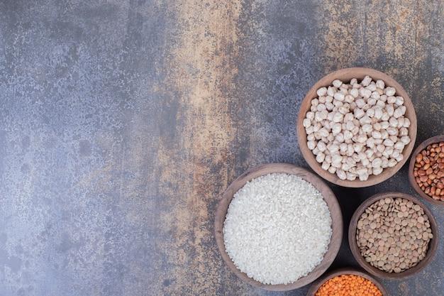 木製のボウルにさまざまな生豆、レンズ豆、ご飯。 無料写真
