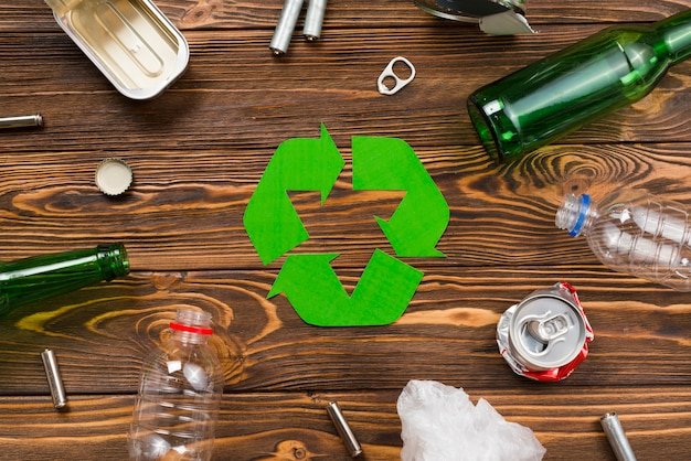 Various reusable trash around recycling symbol Free Photo