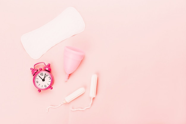 Various sanitary products on pastel pink background. Premium Photo