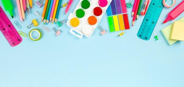Различные поставки школьного офиса и картины на голубой предпосылке. обратно в школу концепции. Premium Фотографии