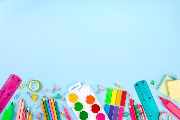 Различные поставки школьного офиса и картины на голубой стене. обратно в школу концепции. вид сверху. копировать пространство Premium Фотографии