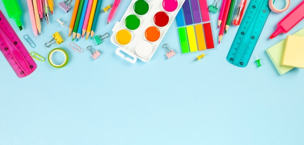 Various school office and painting supplies on blue background. back to school concept. Premium Photo