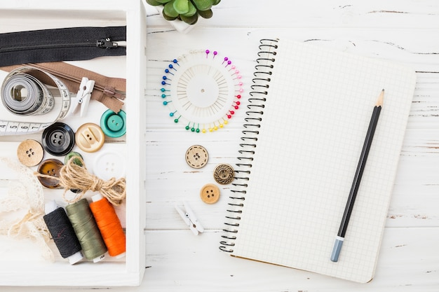 Various sewing accessories with notepad and pencil on wooden background Free Photo