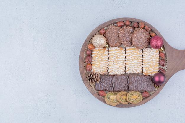 Vari snack e palle di natale su tavola di legno. Foto Gratuite