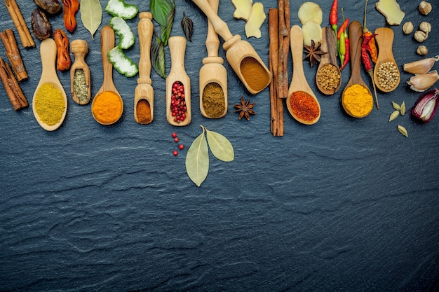 Various of spices and herbs in wooden spoons on the black stone. Premium Photo