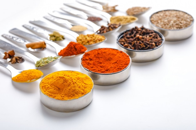 Various spices in spoons on white background Premium Photo