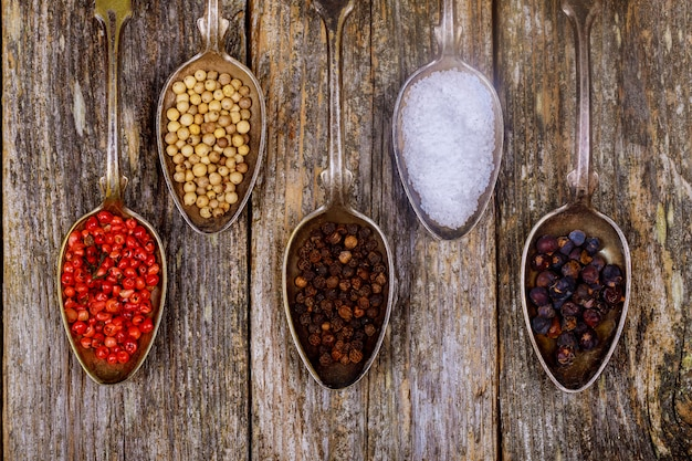 Various spices in wooden spoons on dark brown background. Premium Photo
