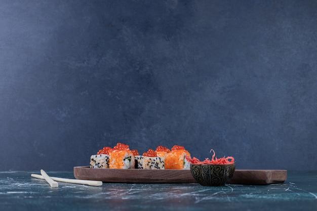 Vari rotoli di sushi decorati con caviale rosso e bacchette. Foto Gratuite