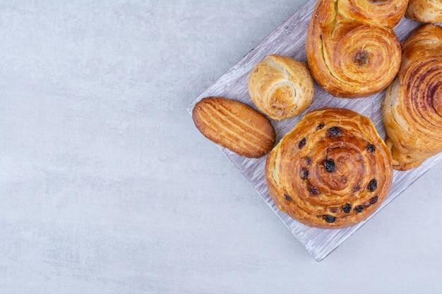 Vari dolci e panini con biscotti sulla tavola di legno. Foto Gratuite