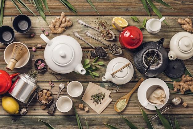 Различный состав чая и чайников, сушеный травяной чай и чай маття на деревянном столе Premium Фотографии