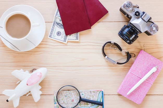 Various traveler accessories with tea cup on wooden background Free Photo