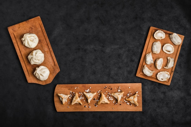 Various type of dumplings on wooden tray against black textured backdrop Free Photo