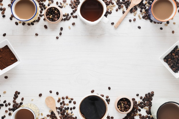 Various types of coffee; raw coffee beans; roasted coffee beans; coffee powder arranged on white table Free Photo