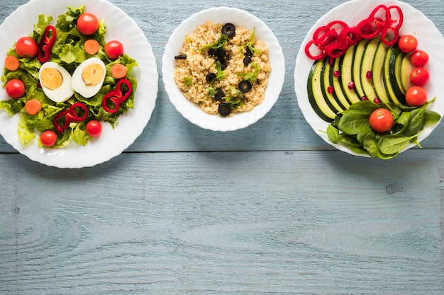 Various types of healthy foods with boiled egg and fresh vegetables arranged in a row Free Photo