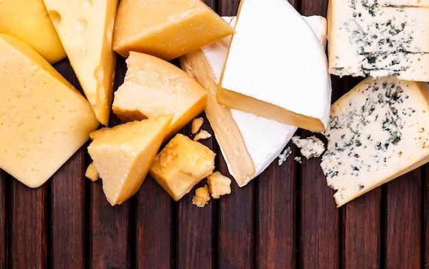 Различные виды сыра на деревянном столе Premium Фотографии