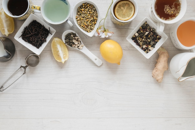 Various types of tea with herbs and dry leaves on wooden table Free Photo