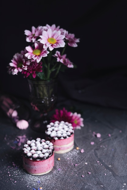 Vase flower with blackcurrant cheese cake with sugar powder dusting Free Photo