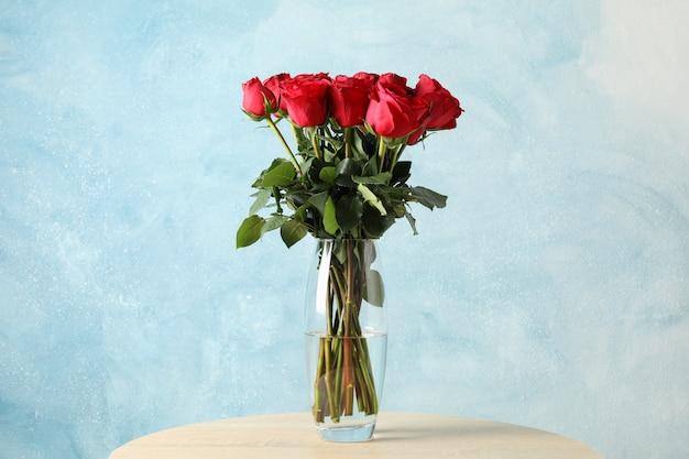 Ваза с букетом красных роз на деревянном столе, место для текста Premium Фотографии