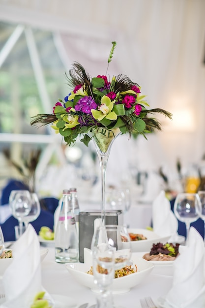 Vase with flowers on a served round table, dinner in a luxurious restaurant Premium Photo
