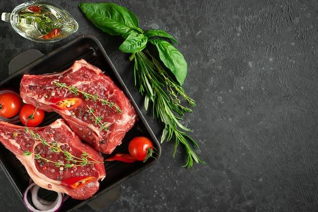 Биток из телячьей кости на сковороде для гриля с овощами, зеленью и оливковым маслом Premium Фотографии